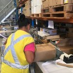 Female employee wearing a yellow high-vis vest completing an order ready for distribution