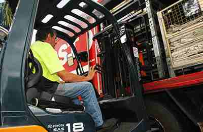 Man operating a forklift to load cages of mail onto an Australia Post collection truck