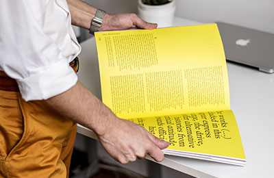 Man examining a black and yellow coloured page layout design in a printed publication