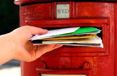 A person's hand inserting several pieces of assorted mail into a red letterbox