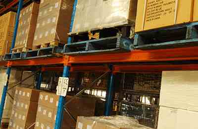 Assorted brown boxes stacked onto pallets and racks in a warehouse