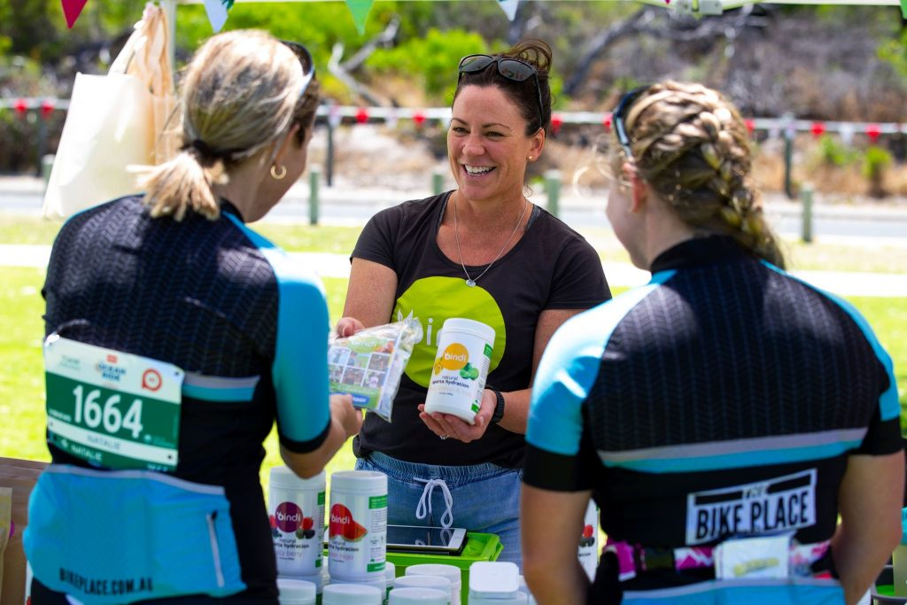 Market Stall with Bindi Nutrition team smiling with two customers